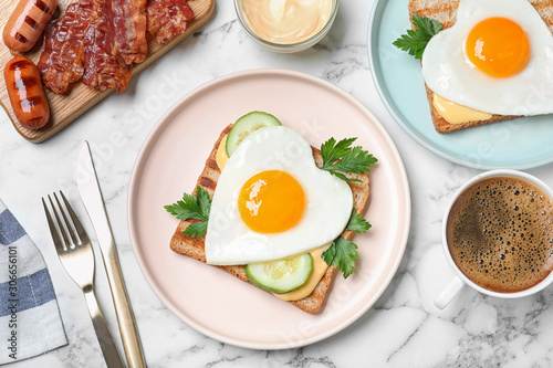 Fototapeta Tasty sandwiches with heart shaped fried eggs for romantic breakfast on white marble table, flat lay obraz