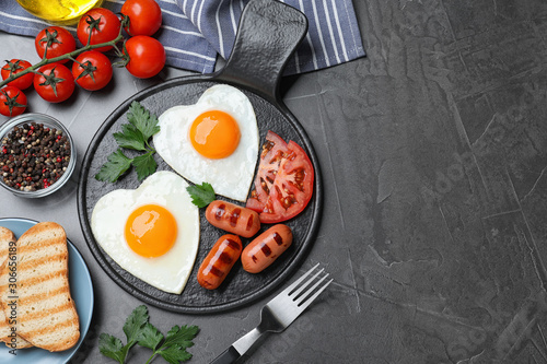 Fototapeta Delicious breakfast with heart shaped fried eggs and  sausages served on dark grey table, flat lay. Space for text obraz