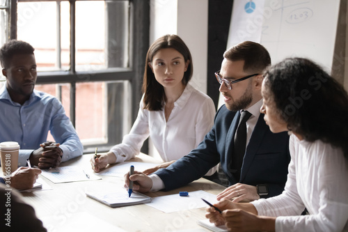 Fototapety, obrazy: Concentrated mixed race young employees listening to confident male ceo.