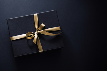 Gift wrapped in dark paper on dark background