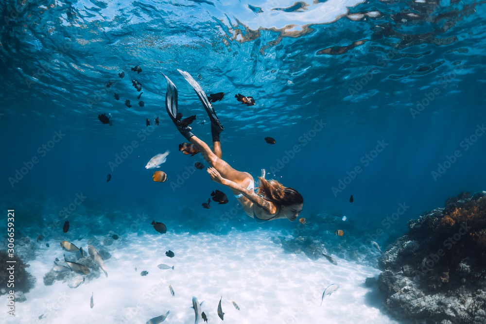Fototapeta Freediver girl with fins glides over sandy bottom with fishes in blue ocean