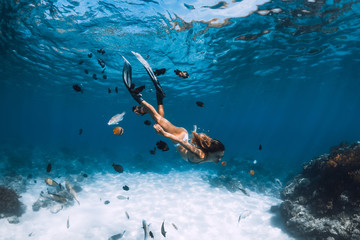 Freediver girl with fins glides over sandy bottom with fishes in blue ocean