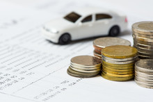 White Car And Coins On The Account Book In Selective Focus, Concept: Buy, New Car, Finance, Investment.