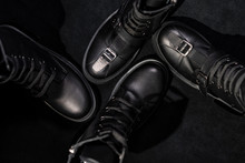 Set Of Black Leather Boots With Buckles And Laces On A Dark Background.