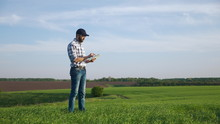 Farmer With A Beard And A Cap Works On The Field In Spring, Use A Digital Tablet. Farmer Using Digital Tablet. Concept Of Technologies.