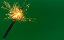 Burning Firework Sparklers On Green Background With Copy Space