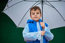 Close Up Portrait Of Boy In Blue Raincoat Hold Umbrella In The Rainy Day