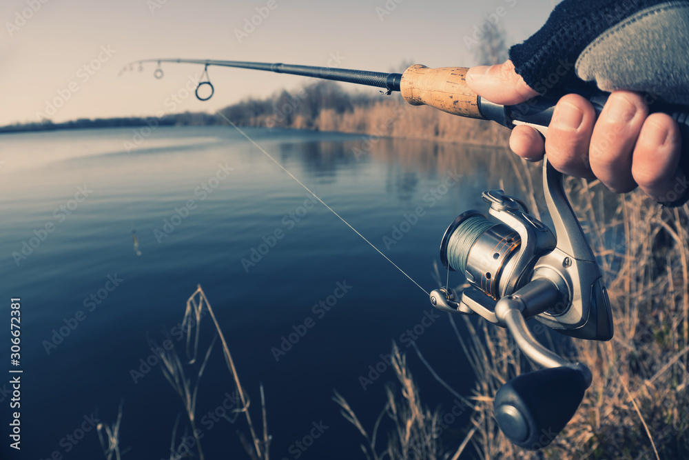 Fototapeta hand with spinning and reel on the summer lake