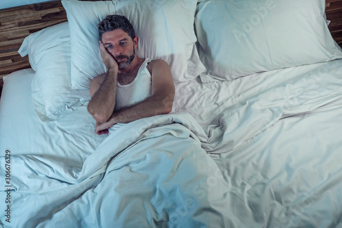 Photo dramatic lifestyle portrait of young attractive sad and depressed man lying on b