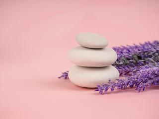Obraz na płótnie Canvas Stack of Zen stones on abstract pink background. Relax still Life with folded stones. Zen pebbles, stones, Spa-calm scenes to slow life. with vegetation, ecological concept