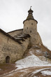 The ancient medieval fortress is located on the river Bank. The fortress is covered with fallen snow. Pskov, Russia.