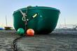 Leinwanddruck Bild - gruenes boot liegt auf dem strand mit zwei bojen