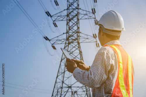 Fotografia Electrical engineer holding and using a digital tablet with high voltage tower background