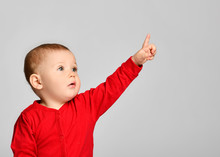 Little Toddler Boy Points Finger Up Side In Red Infant Bodysuit With Free Text Space On Gray