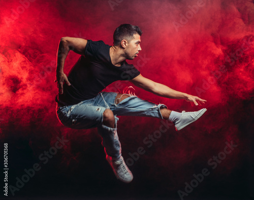 Photographie portrait of vigorous dancer male dancing street dance, jump in the air isolated