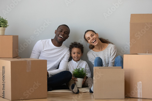 Overjoyed mixed race family sitting on floor near cardboard boxes.
