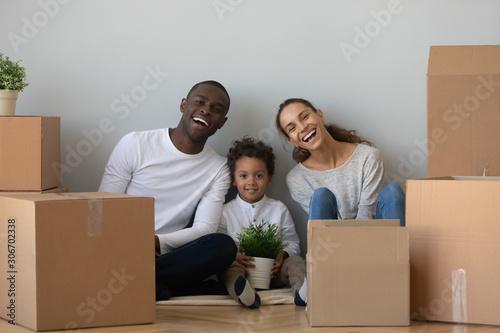 Fototapeta Overjoyed mixed race family sitting on floor near cardboard boxes. obraz