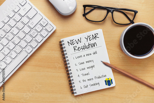фотография New Year Resolution Goal List 2020 - Business office desk with notebook written in handwriting about plan listing of new year goals and resolutions setting