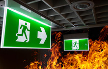 Hot Flame Fire And Green Fire Escape Sign Hang On The Ceiling In The Office At Night. The Concept Of Fire Escape Training And Preparation For Evacuation