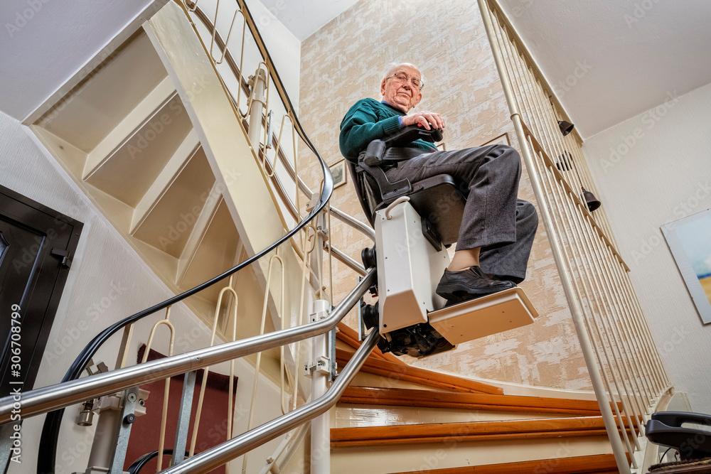 Fototapeta Elderly Man in the Staircase Using the Stairlift