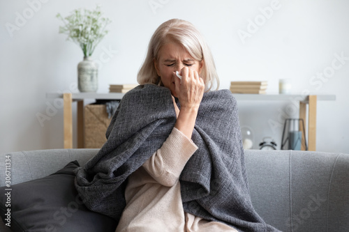 Fotografie, Tablou Aged sick woman sneezing holding napkin blow out runny nose