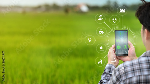 A male farmer is working in the field his using a mobile phone with Innovation technology for smart farm system Fotobehang