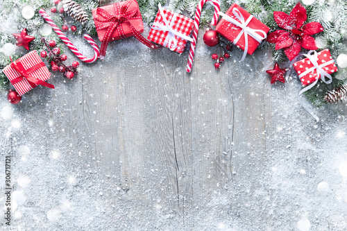 Christmas and New Year background with fir branches, gift boxes, ornament and snowfall - 306717121
