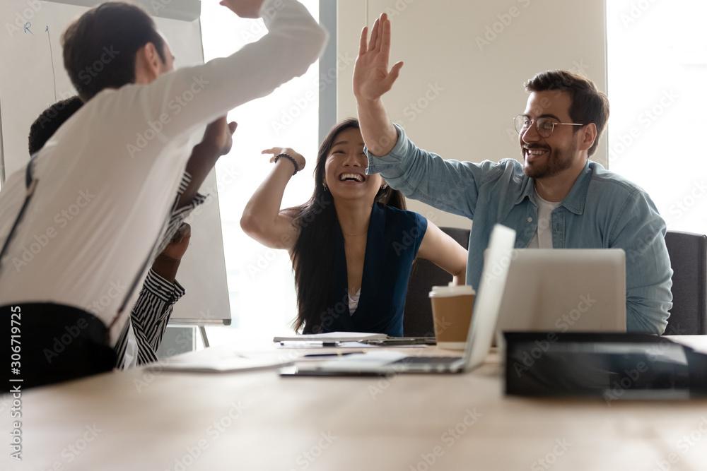 Fototapeta Multi-ethnic businesspeople giving high five celebrating closing profitable deal