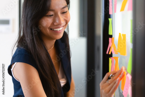 Photo Asian worker preparing boardroom attaching sticky coloured reminders on glass