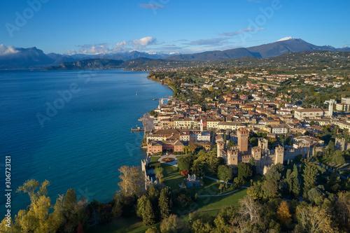 Aerial view of Lake Garda and the city center of Lazise, Italy. Autumn season, blue sky, Monte Baldo on the horizon, snow in the mountains