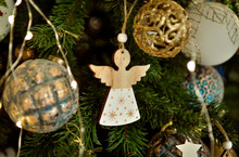 Christmas Angel. Toy Angel Made Of Wood Hanging On A Christmas Tree. New Year's Decor.
