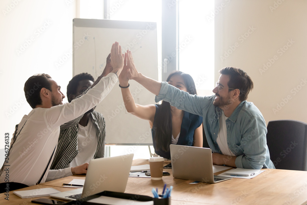 Fototapeta Multiethnic work team give high five motivated for shared success