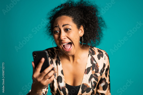 Angry trendy african woman screaming down her mobile phone in studio Wallpaper Mural