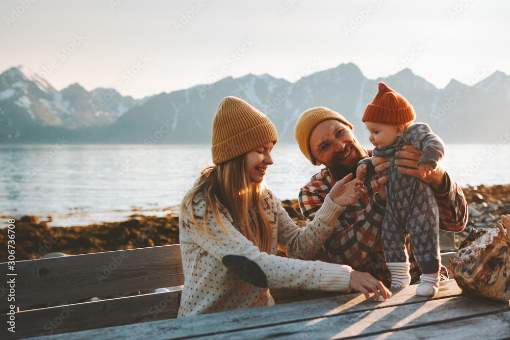 Fototapeta Happy family outdoor mother and father with baby traveling together vacation parents playing with child healthy lifestyle mountains view in Norway