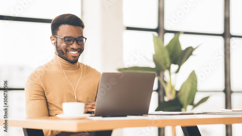 Smiling black student in glasses studying in bar - 306738506