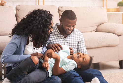 Photo Loving afro parents tickling their little daughter, having fun at home