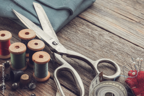 Fototapeta Retro sewing items: tailoring scissors, cutting knife, thimble, wooden thread spools, cushion for including pins, fabrics and sewing accessories