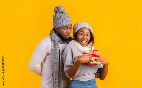 Photo Happy afro winter girl holding Christmas gifts, boyfriend staying behind