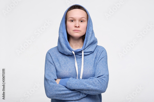 Emotionless, unsentimental phlegmatic caucasian teenager with serious look looking at camera Slika na platnu
