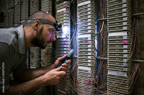 Fotografía  A technician with a flashlight on his head works in a dark server room
