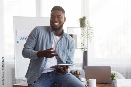 Smiling black manager holding digital tablet, explaining something to his colleagues