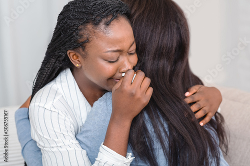 Fotografía Girl hugging and consoling her crying friend at home