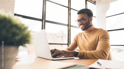 Cuadros en Lienzo Satisfied african american manager typing on keyboard