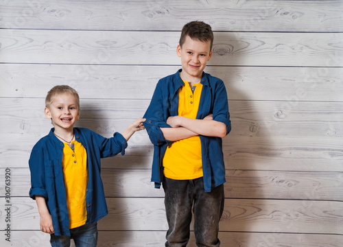 Two boys in casual clothes in white wooden background looking at camera Wallpaper Mural