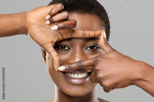 Photo Beautiful african woman holding frame from fingers near her eyes