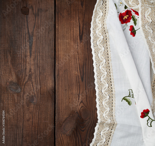 Fototapeta embroidered white dishcloth with lace on a brown wooden background