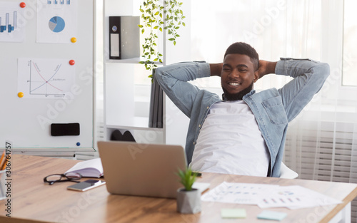 Fotomural Black businessman leaning back on chair in office after successful work