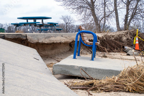 Michigan blue park bench on broken concrete slab after storm erosion Canvas Print