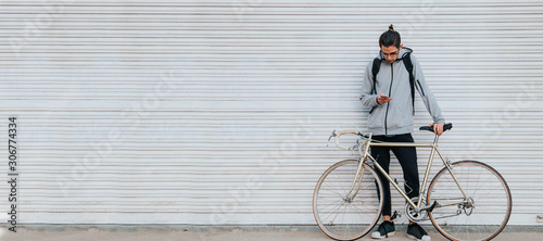 Fototapeta young man with mobile phone in the street and vintage bicycle with space for text or announcements obraz