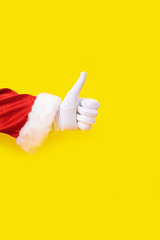 Santa Claus glove hand yellow background one red suit copy space